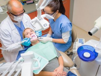 Professional dentist and nurse check teeth female patient dental surgery